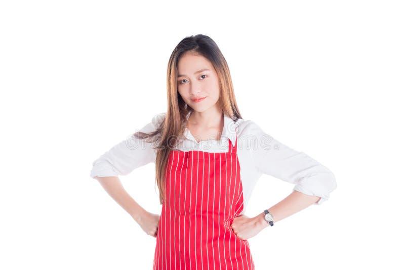 Belle femme asiatique portant le tablier rouge et regardant l'appareil-photo photo stock