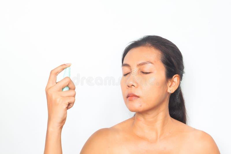 Belle femme asiatique pulvérisant l'eau minérale sur son visage Beaut? et sant? photos libres de droits