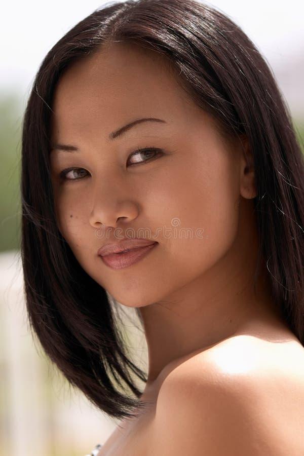 Belle femme asiatique regardant au-dessus de l'épaule photos libres de droits