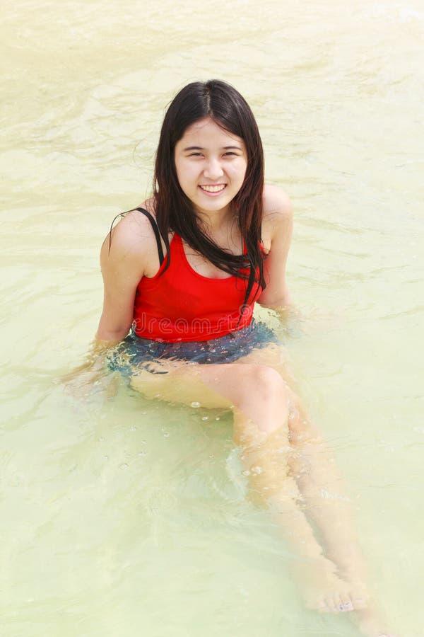 Belle femme asiatique s'asseyant sur la plage images stock