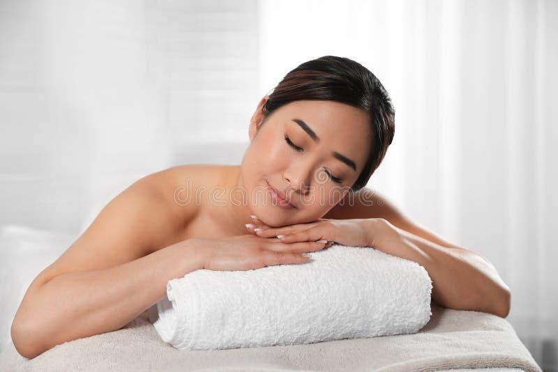 Belle femme asiatique se trouvant sur la table de massage photo stock