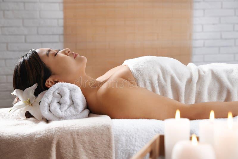 Belle femme asiatique se trouvant sur la table de massage images stock