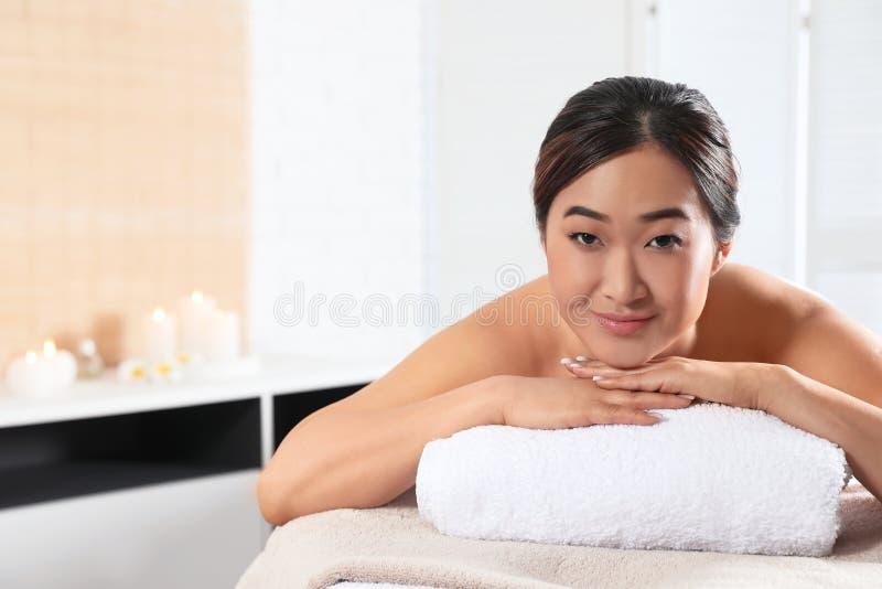 Belle femme asiatique se trouvant sur la table de massage dans le salon de station thermale image stock