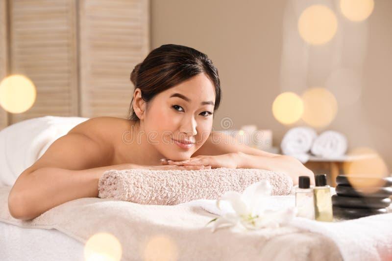 Belle femme asiatique se trouvant sur la table de massage dans le salon de station thermale photo stock