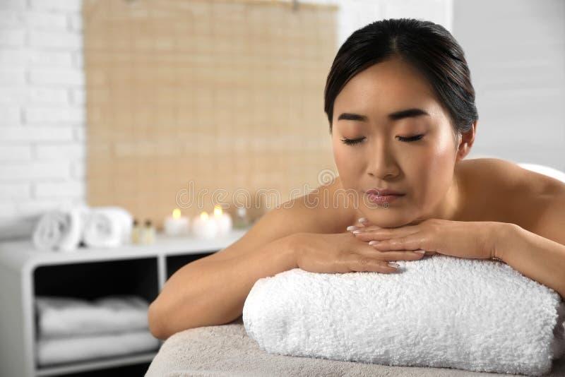 Belle femme asiatique se trouvant sur la table de massage dans le salon de station thermale photos libres de droits