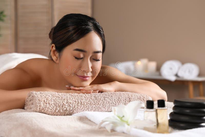 Belle femme asiatique se trouvant sur la table de massage dans le salon de station thermale images stock