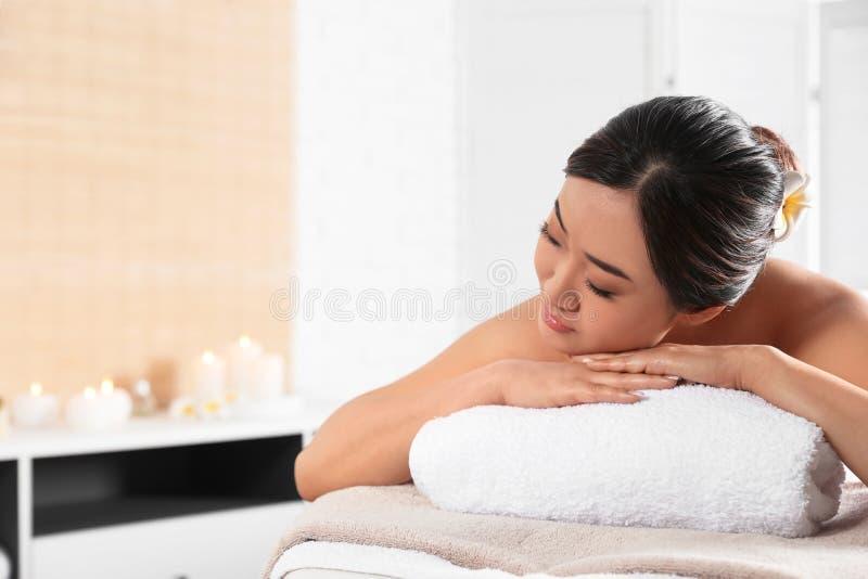 Belle femme asiatique se trouvant sur la table de massage dans le salon de station thermale images libres de droits