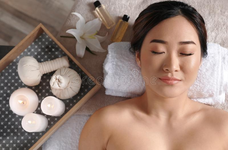 Belle femme asiatique se trouvant sur la table de massage dans le salon photo libre de droits