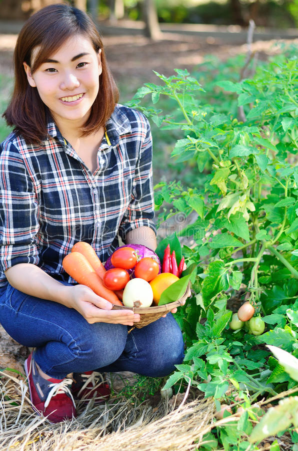 Belle femme asiatique tenant le seau de légume frais images stock