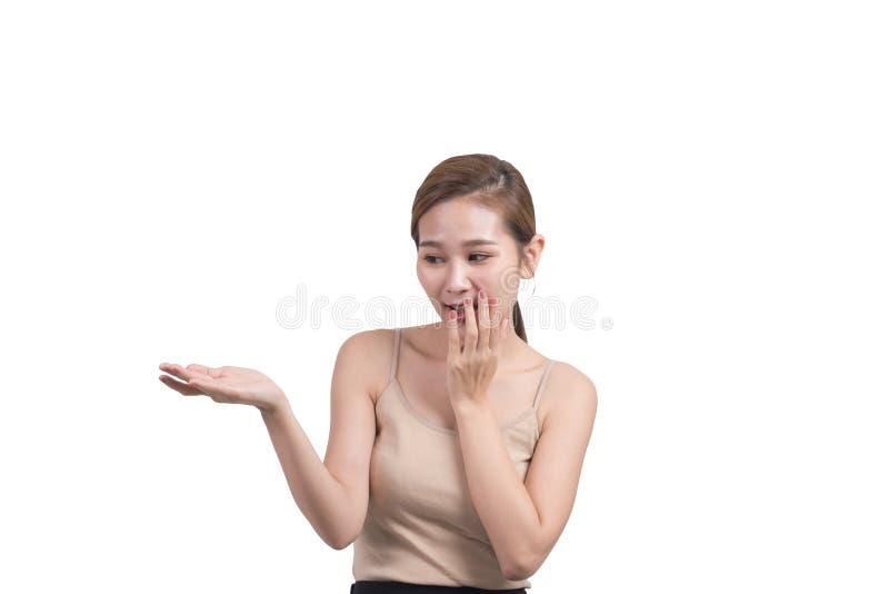 Belle femme asiatique tenant quelque chose dans sa main et regardant votre produit avec grande joie, enthousiaste très heureux photographie stock libre de droits