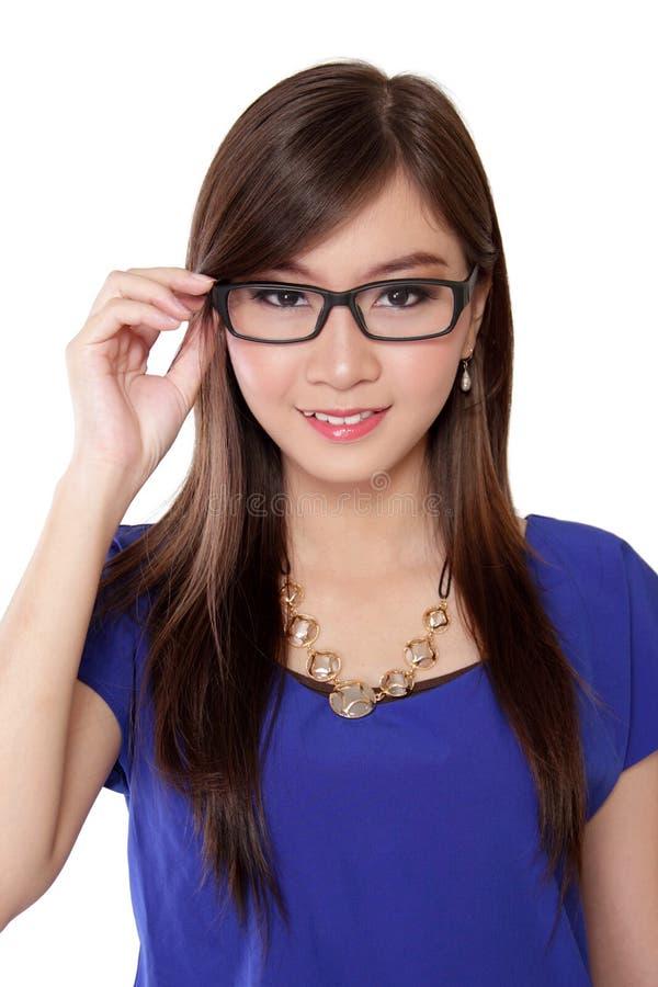 Belle femme asiatique tenant ses verres, d'isolement sur le blanc photo stock