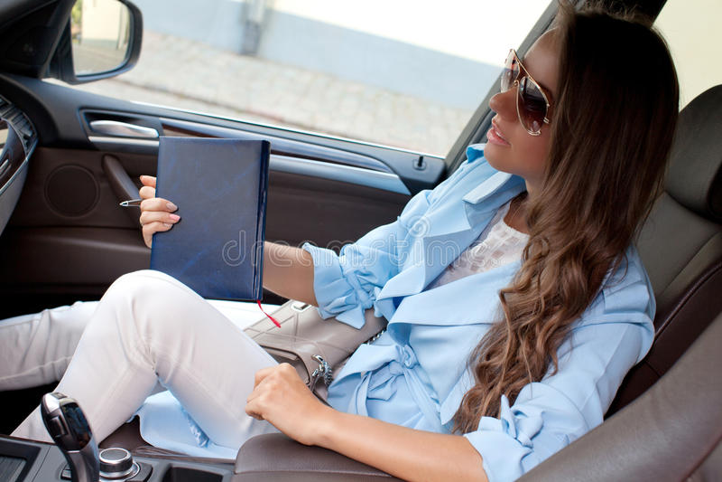Belle femme assez jeune s'asseyant dans la voiture photographie stock libre de droits