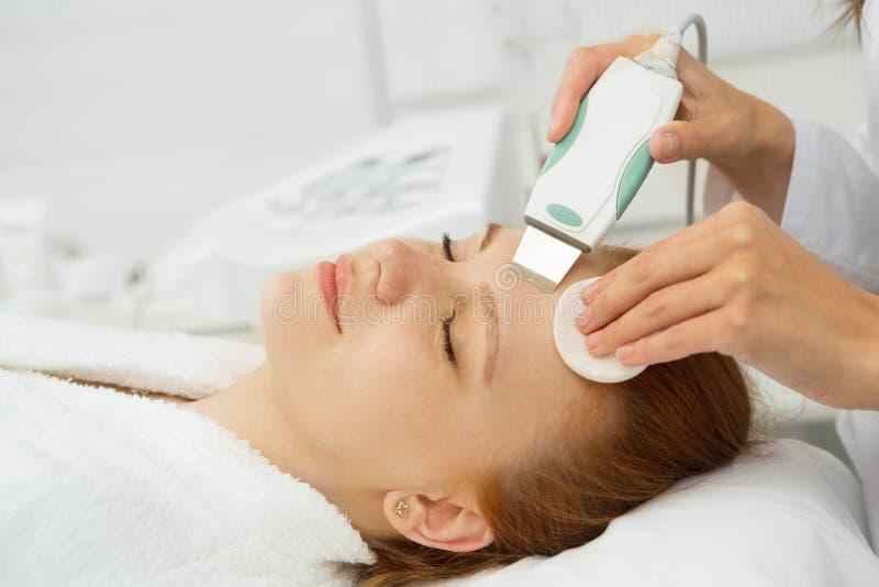 Belle femme atteignant à ultrason le nettoyage facial le Cl de beauté photos stock