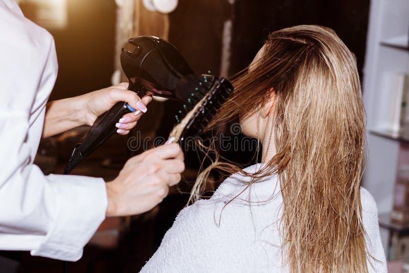 Belle femme attirante blonde au coiffeur image stock