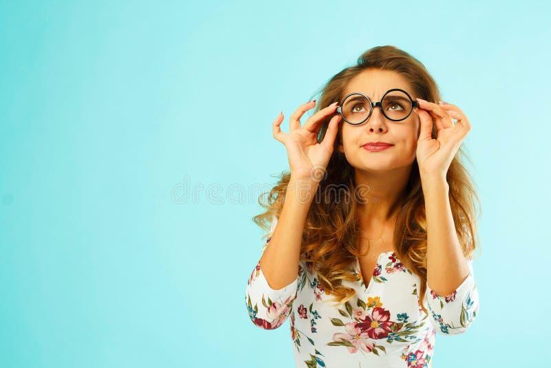 Belle femme attirante en verres ronds au-dessus de fond bleu photo stock