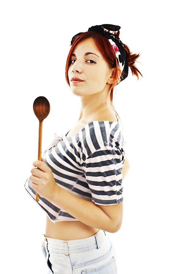 Belle femme au foyer de pin-up de style avec la cuillère en bois image libre de droits