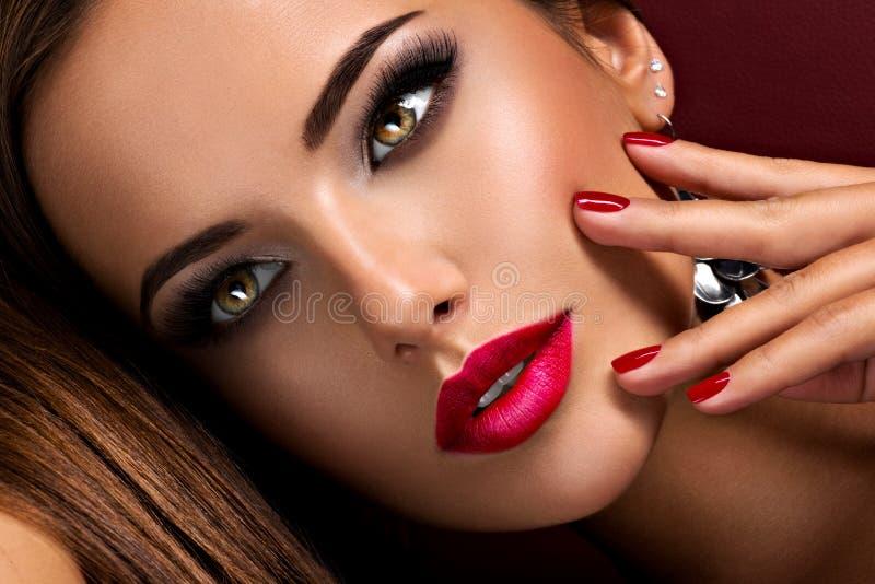 Belle femme au maquillage d'oeil brillant et aux lèvres rouges allongée sur le canapé photos stock