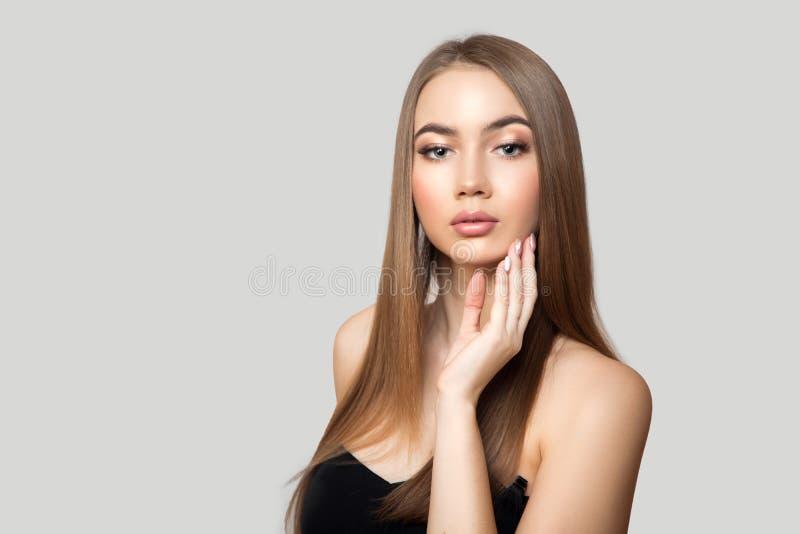 Belle femme aux cheveux brillants droits et maquillage Portrait sur fond gris Nettoyer photographie stock