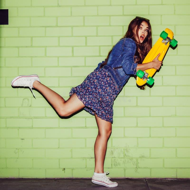 Belle femme aux cheveux longs avec un shortboard de penny de couleur près d'a photographie stock libre de droits