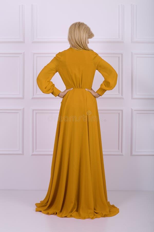 Belle femme aux cheveux longs dans la robe jaune image libre de droits