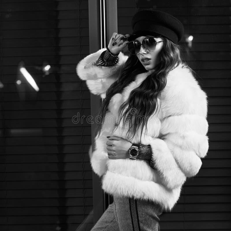 Belle femme aux cheveux longs dans le chapeau, les lunettes de soleil et le coa blanc de fourrure photographie stock libre de droits