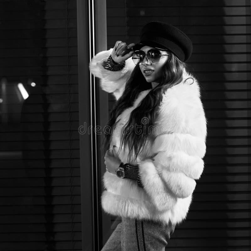 Belle femme aux cheveux longs dans le chapeau, les lunettes de soleil et le coa blanc de fourrure photographie stock