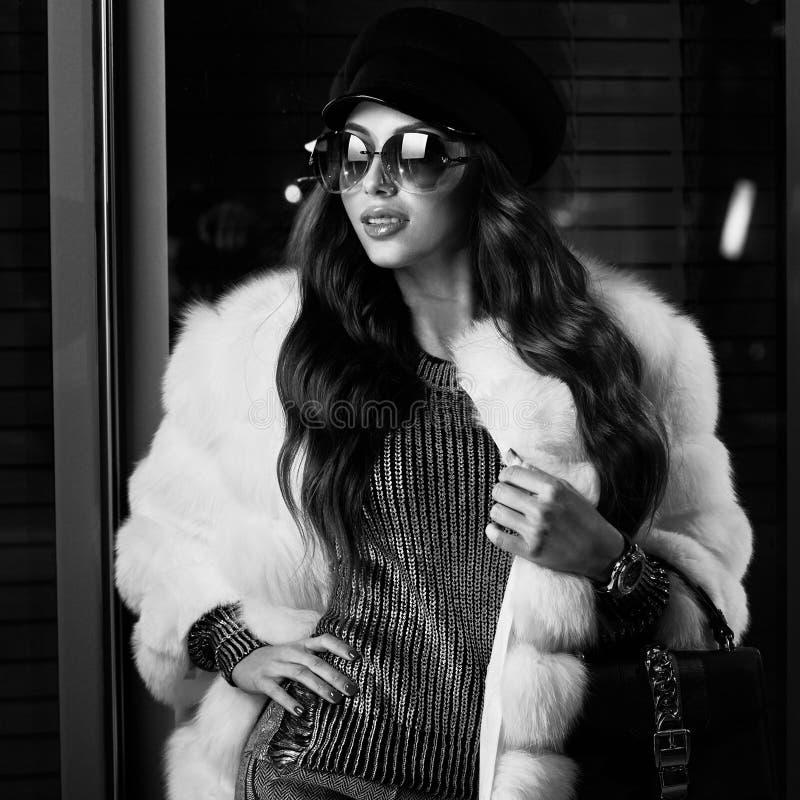 Belle femme aux cheveux longs dans le chapeau, les lunettes de soleil et le coa blanc de fourrure photo stock