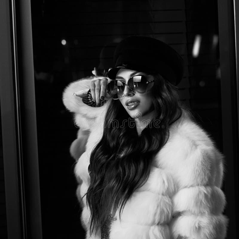 Belle femme aux cheveux longs dans le chapeau, les lunettes de soleil et le coa blanc de fourrure photos libres de droits