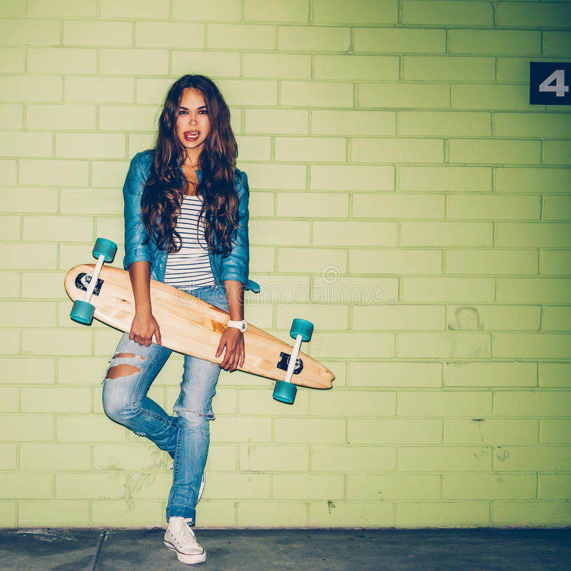 Belle femme aux cheveux longs près d'une brique verte photographie stock libre de droits