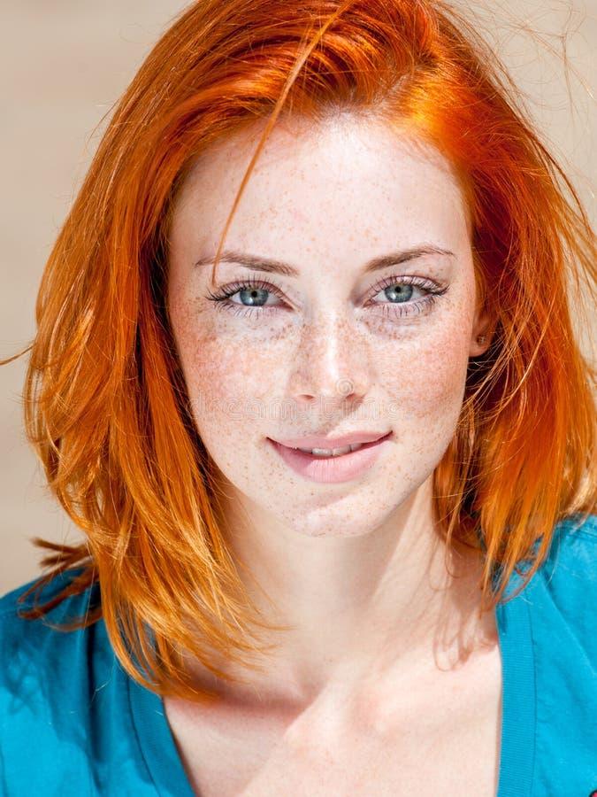 Belle femme aux yeux bleus couverte de taches de rousseur rousse photographie stock libre de droits