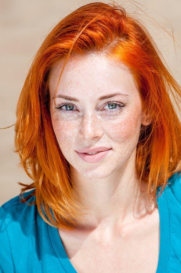 Belle femme aux yeux bleus couverte de taches de rousseur rousse images stock