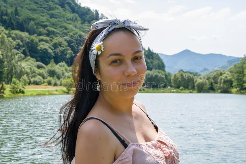 Belle femme avec Daisy dans les cheveux et maillot de bain sur fond de montagnes et de lac, vacances d'été à la station photos libres de droits