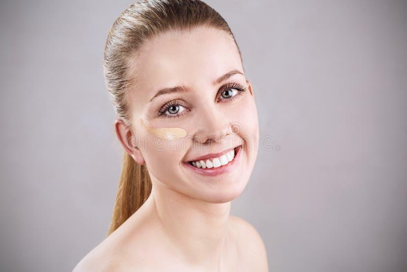 Belle femme avec de la crème de base sur le visage image libre de droits