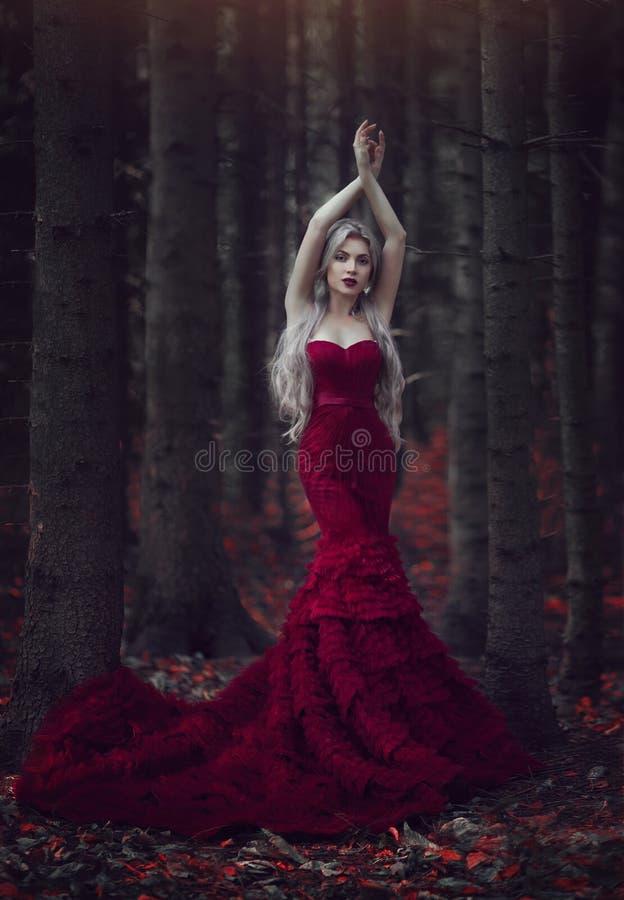 Belle femme avec de longs cheveux blancs posant dans une robe rouge luxueuse avec un long train se tenant dans une forêt de pin d photographie stock
