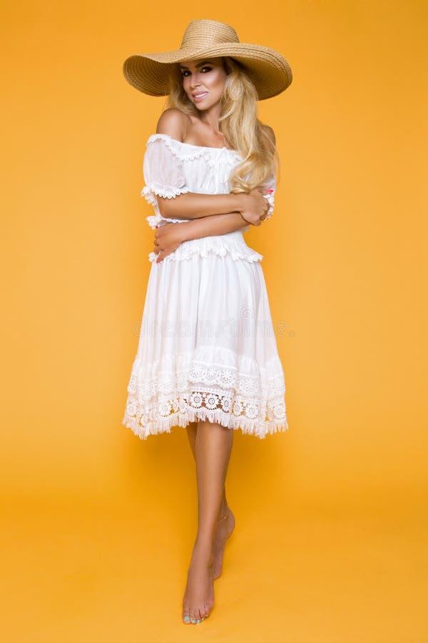 Belle femme avec de longs cheveux blonds, utilisant une robe et un chapeau blancs images libres de droits