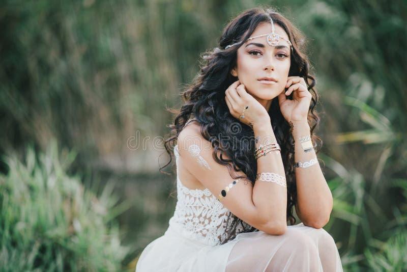 Belle femme avec de longs cheveux bouclés habillés dans la robe de style de boho posant près du lac photo stock