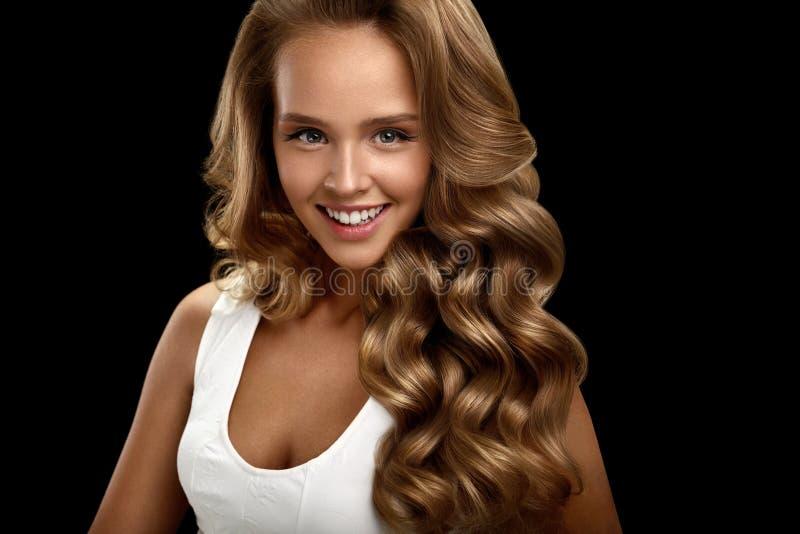 Belle femme avec de longs cheveux bouclés onduleux blonds brillants beauté images libres de droits