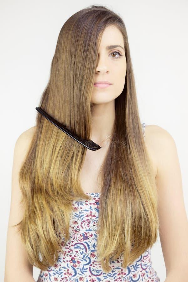 Belle femme avec de longs cheveux avec des actions de peigne dans elles photos stock