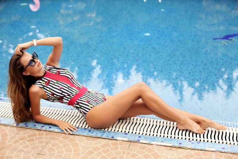 Belle femme avec de longs cheveux foncés dans le costume de natation, n de détente photo libre de droits