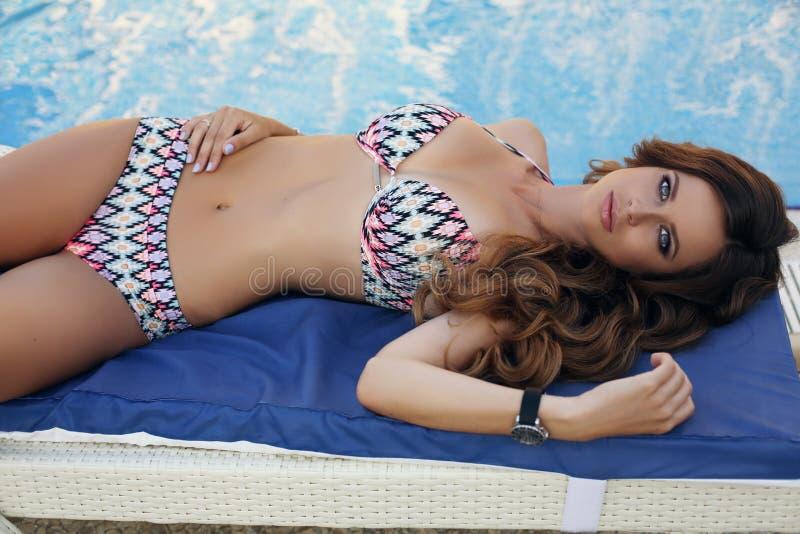 Belle femme avec de longs cheveux foncés dans le costume de natation, n de détente photo stock