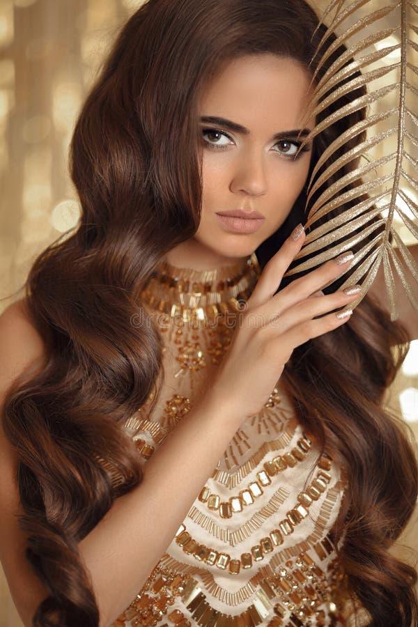 Belle femme avec de longs cheveux onduleux, ongles d'or de manucure et e photo libre de droits