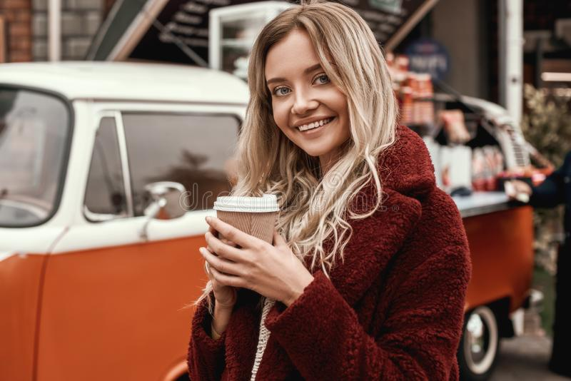 Belle femme avec de longs cheveux posant avec le sourire timide et le café potable photographie stock libre de droits