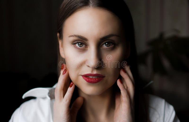 Belle femme avec de longs poils droits bruns et ongles rouges photos stock