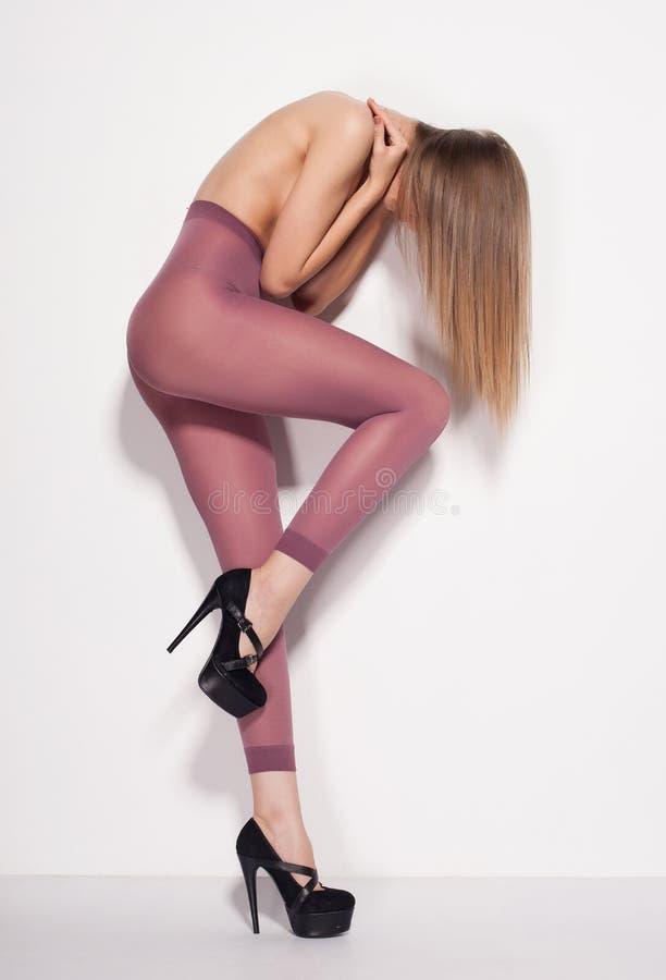 Belle femme avec de longues jambes sexy portant seulement des bas dans le studio - plein corps image stock