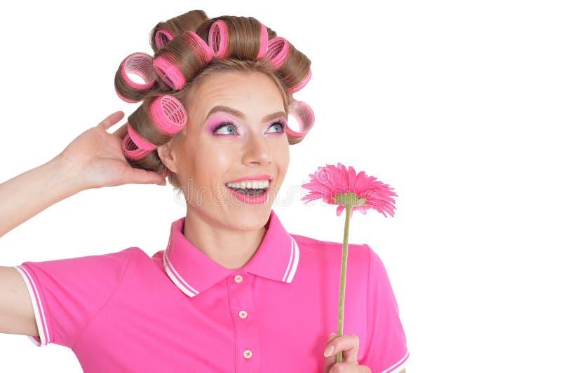 Belle femme avec des bigoudis de cheveux jugeant la fleur de gerbera d'isolement images stock
