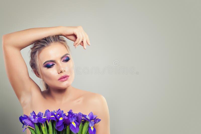 Belle femme avec des fleurs d'iris Madame avec la peau parfaite, le maquillage coloré et la main sur le fond de bannière avec l'e image libre de droits