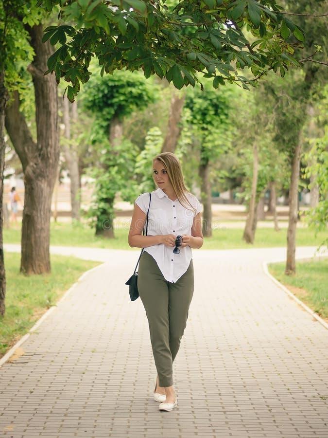 Belle femme avec des lunettes de soleil dans sa main regardant au côté, marchant le long du chemin en parc photos libres de droits