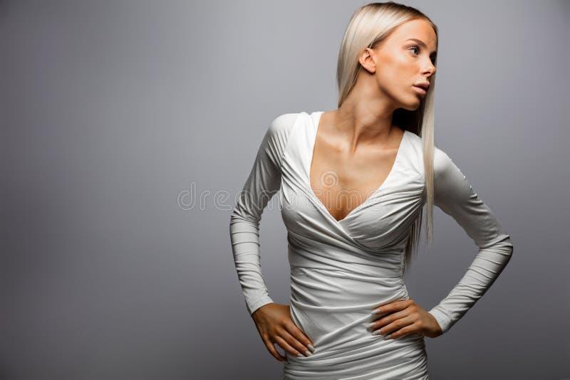 Belle femme avec des mains sur la hanche regardant loin photographie stock