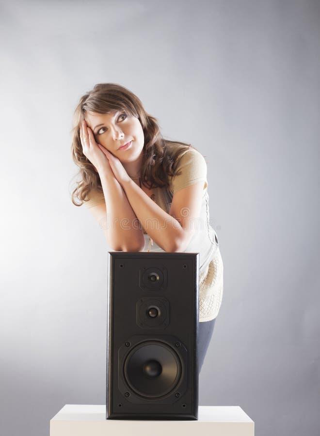 Belle femme avec des mains sur le grand haut-parleur en bois photos stock