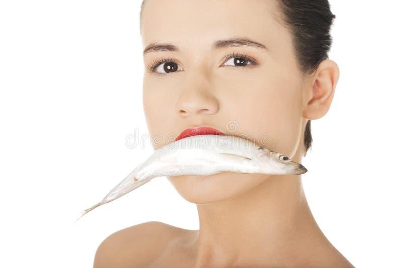 Belle femme avec des poissons dans sa bouche images libres de droits